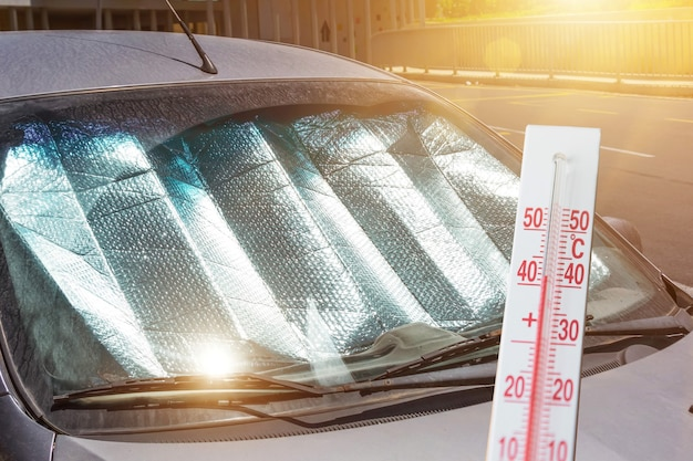 Protective reflective surface under the windshield of the passenger car parked on a hot day, heated by the sun's rays. the thermometer shows the temperature inside the car.