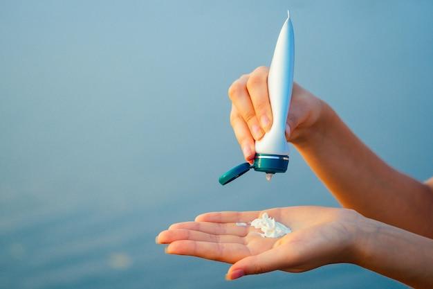 여자의 손에 바다에 보호 썬 크림.
