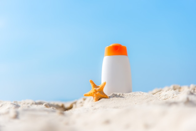 Protective sunscreen or sunblock and sunbath lotion in white plastic bottles on tropical beach, summer accessories in holiday, copy space.  summer concept