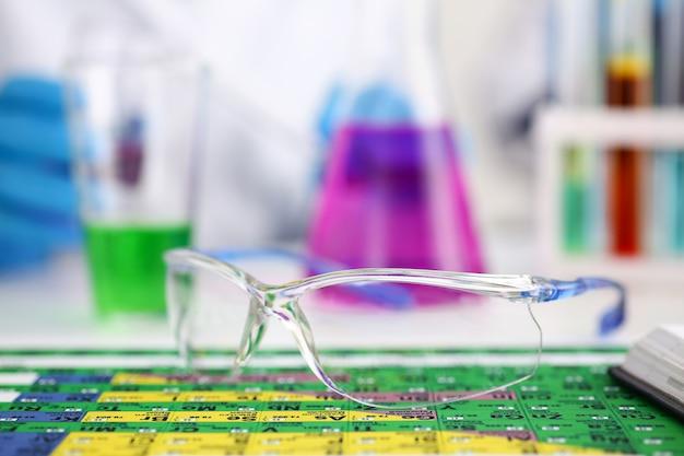 周期表の上に横たわる保護手術用メガネまたは実験用メガネ