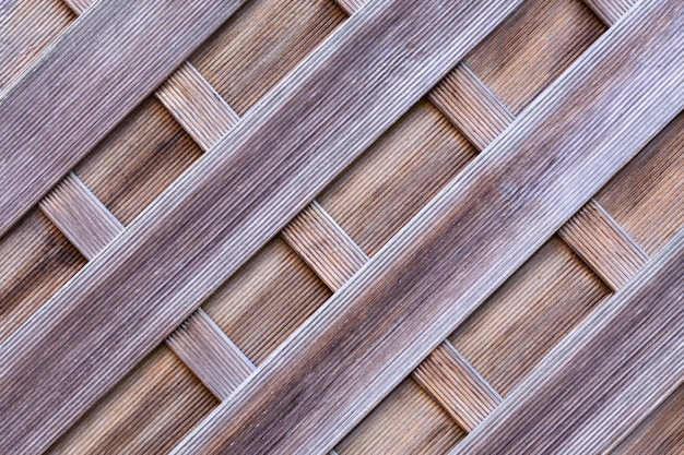 Protective wall of wooden picket fence with a grooved surface.