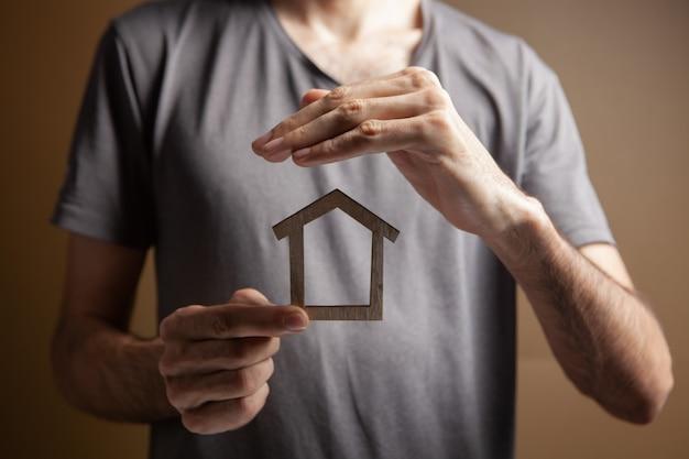 갈색 배경에 손으로 집을 보호합니다.