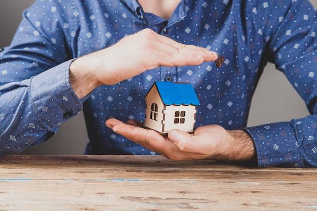 Защищает дом руками