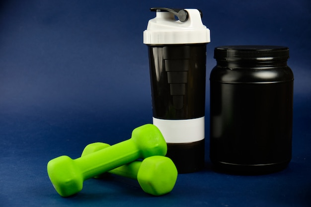 Protein in a black jar, plastic shaker, green dumbbells and omega-3 cans