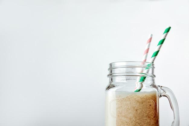 Протеиновый коктейль с молочной ванилью в стеклянной банке с трубочкой