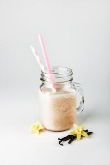 빨대와 함께 유리 항아리에 우유 바닐라와 단백질 칵테일