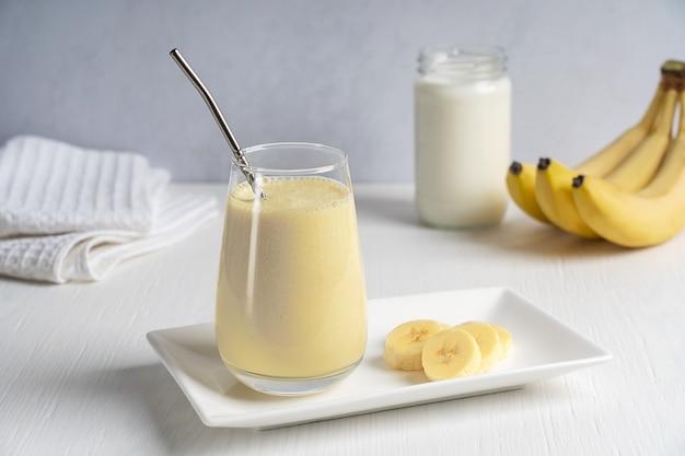 Белковый энергетический банановый молочный коктейль в стакане с металлической трубочкой на белом деревянном столе