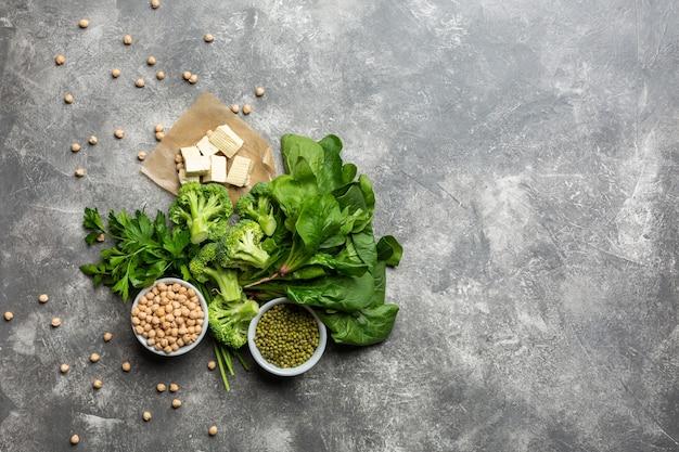 菜食主義者のためのタンパク質:具体的な背景に豆腐、野菜、ナッツ、種子、豆類の上面図。コンセプト:健康的なきれいな食品。
