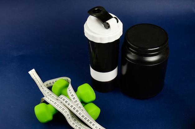 黒い瓶に入ったタンパク質、プラスチックシェーカー、緑色のダンベル、オメガ3缶