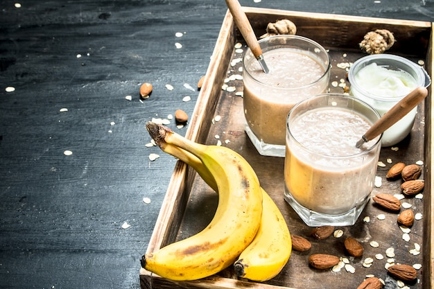 Protein smoothie with banana and nuts on black background
