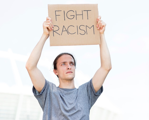 Protester holding fight racism quote on cardboard