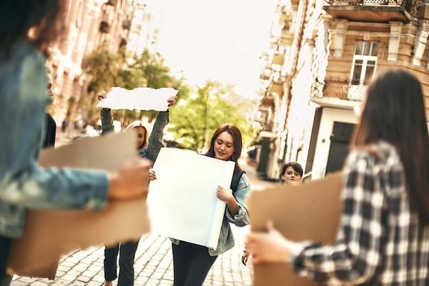 야외에서 시위하는 동안 간판을 들고 있는 긍정적인 여성 활동가 그룹