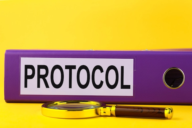 Protocol, blue folder in the office on a yellow background.