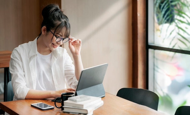 Protrait молодой и умной женщины в очках, работающих на компьютере с счастьем, оставаясь дома, работая из дома концепции.