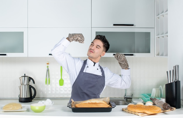 자랑스럽고 야심 찬 남성 요리사가 흰색 부엌에서 홀더와 갓 구운 빵을 입고 유니폼을 입었습니다.