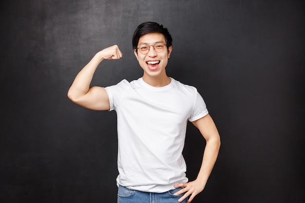 Гордый и хвастливый красивый азиатский парень тренируется в спортзале, демонстрирует бицепс своей подруге, насколько он силен, доволен улыбкой, занимается спортом, тренируется как образец для подражания спортсмена,