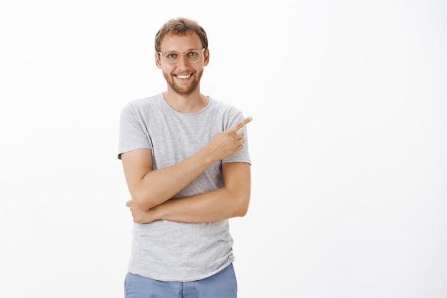 Гордый и довольный красивый творческий работодатель демонстрирует новый продукт компании, хвастаясь и указывая на верхний правый угол с довольной дружелюбной улыбкой.