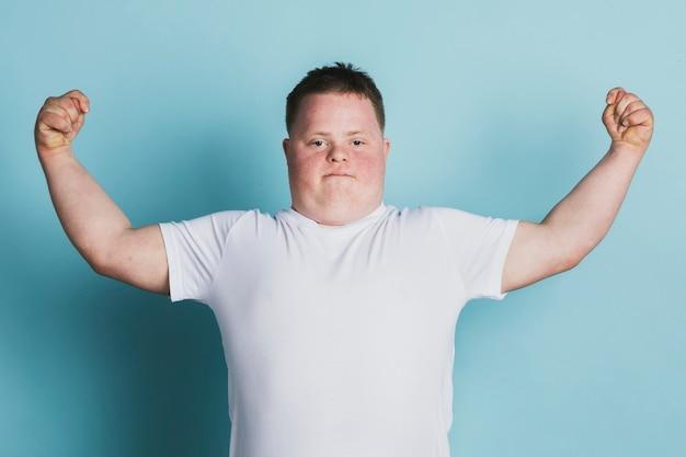 팔을 구부리는 다운증후군을 가진 자랑스러운 소년