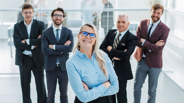 Proud business woman standing in front of a business team. success concept