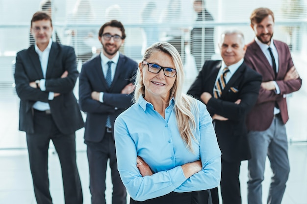 Proud business woman standing in front of a business team