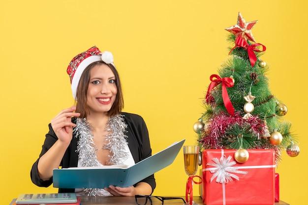 Orgogliosa signora affascinante in vestito con cappello di babbo natale e decorazioni di capodanno che tengono documento in ufficio su giallo isolato