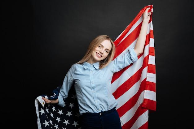 Гордая веселая счастливая девушка веселится и улыбается, держа национальный флаг и стоя изолированной в черной стене