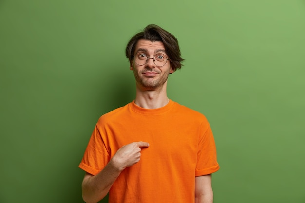 Proud cheerful man points at himself and asks who me, has pleased expression, dressed in bright orange t shirt, round transparent glasses, isolated on green wall, boasts about his achievements