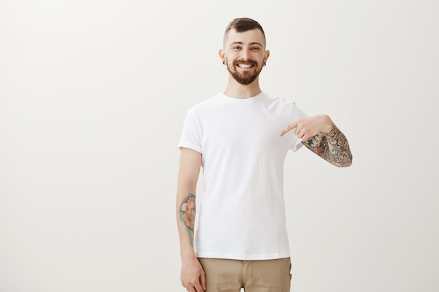 Proud cheerful man with tattoos pointing at himself and smiling pleased
