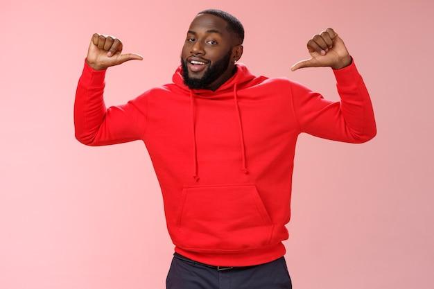 赤いパーカーを着た誇り高き自信に満ちた傲慢な見栄えの良いアフリカ系アメリカ人のひげを生やした男性の同僚は、ピンクの壁に立って、自分自身を自慢しているように生意気な話の成果を指して親指を上げます