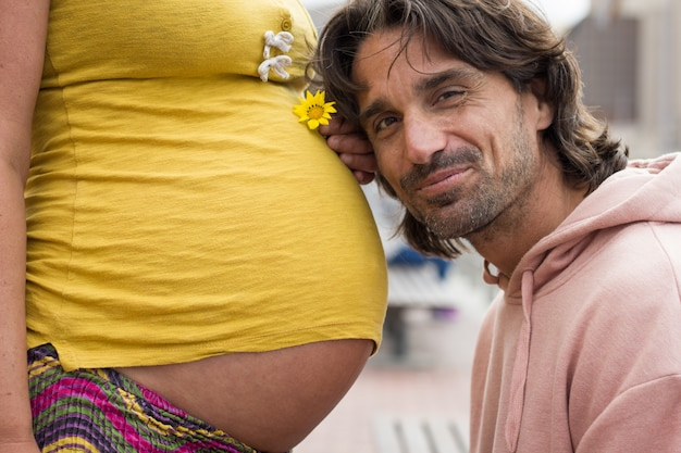 誇り高きパパは黄色い花を持っている妊娠中の母親に頭をもたせます。家族の新しいメンバーを待っている興奮した父。