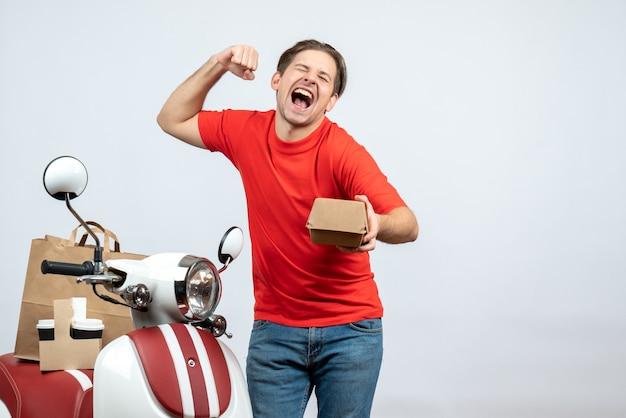 Orgoglioso fattorino in uniforme rossa in piedi vicino a scooter tenendo piccola scatola su sfondo bianco