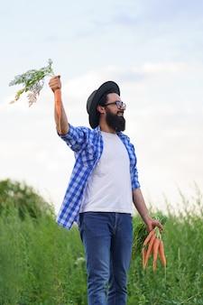緑の野原と空のカメラにニンジンの収穫を示す誇り高き農夫