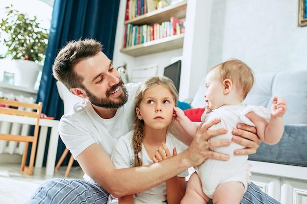 自宅で彼の生まれたばかりの赤ちゃんの娘を持つ父親