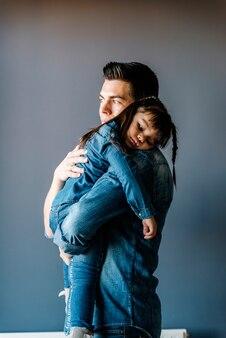 자랑스러운 아버지는 집에서 딸을 안아줍니다.