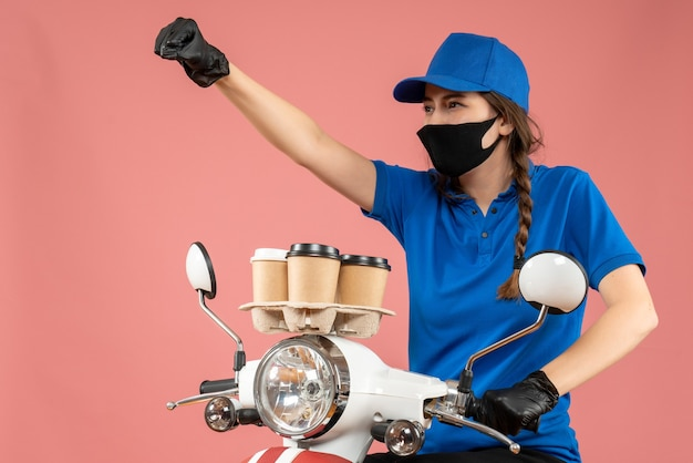 Proud female courier wearing black medical mask and gloves delivering orders on peach background