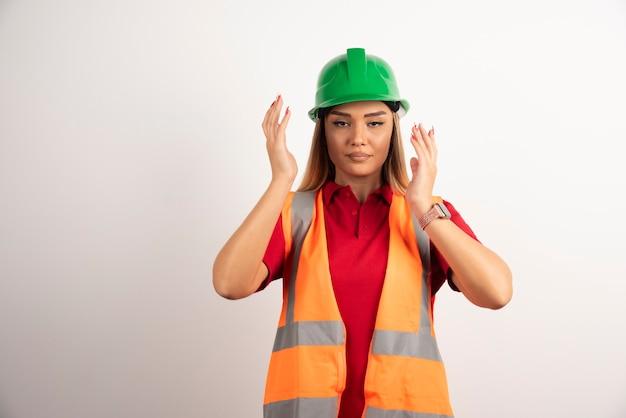 Lavoratrice orgogliosa in posa con casco verde su sfondo bianco.
