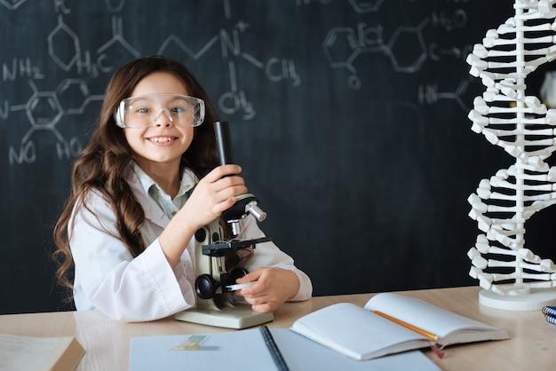 Горжусь своим первым успехом. улыбающийся счастливый опытный ребенок стоит в лаборатории и наслаждается уроками медицины, принимая участие в научном проекте и используя микроскоп