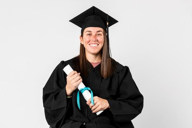 Гордая девушка в выпускном платье держит диплом