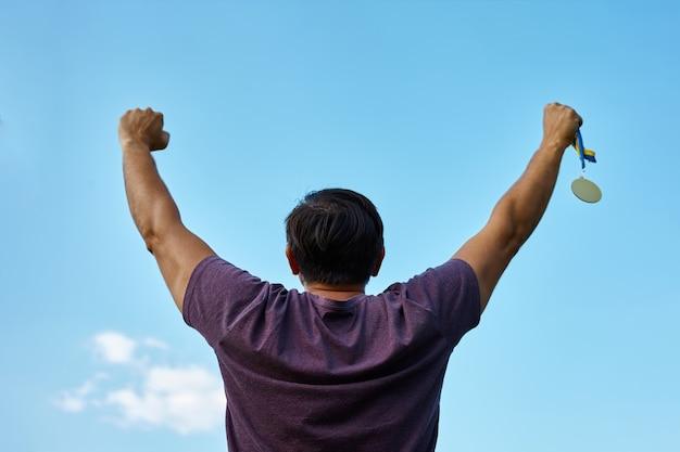 腕を上げて勝利を祝う誇り高き金メダル男
