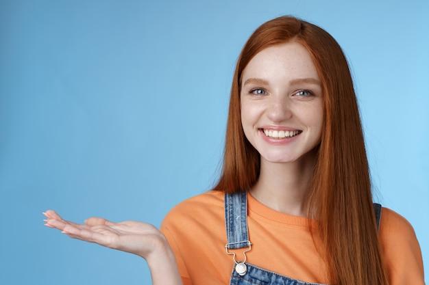 誇り高き見栄えの良い自信のある赤毛の女の子は素晴らしい製品を保持しますオブジェクトを保持します手のひらを上げる手空白の青いコピースペース笑顔喜んでクールなリンクをお勧めします、立っているスタジオの背景が役立ちます。