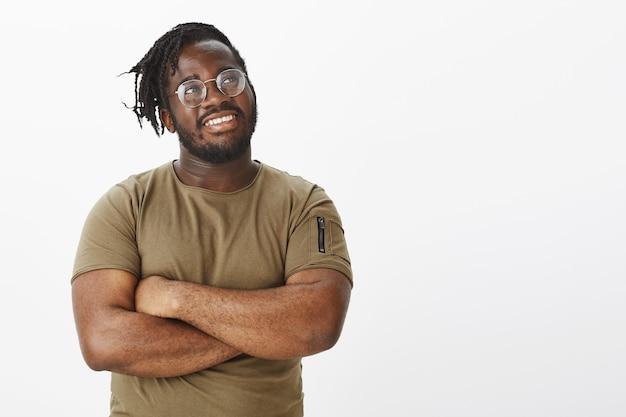 Ragazzo orgoglioso con gli occhiali in posa contro il muro bianco