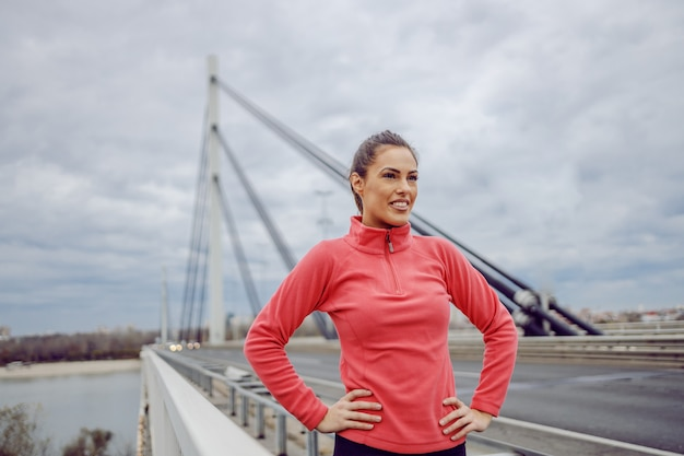 Proud handsome young sporty brunette standing on the bridge with hands on hips and taking a break from running. urban life. outdoor fitness on cloudy weather concept.