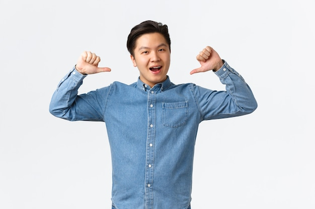 Proud and happy asian guy show-off, pointing at himself and smiling delighted, celebrate personal achievement, bragging, become champion, feeling success, standing white background.