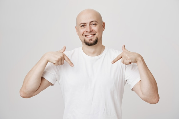 Гордый счастливый лысый мужчина средних лет указывая на себя и улыбаясь