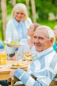 Proud to have a big family. happy family sitting at the dining table outdoors while senior man looking over shoulder and smiling