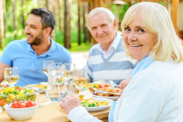 Proud to have a big family. happy family sitting at the dining table outdoors while senior woman looking over shoulder and smiling