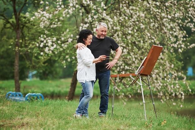 Гордый муж. пожилая пара отдыхает и вместе работает над краской в парке