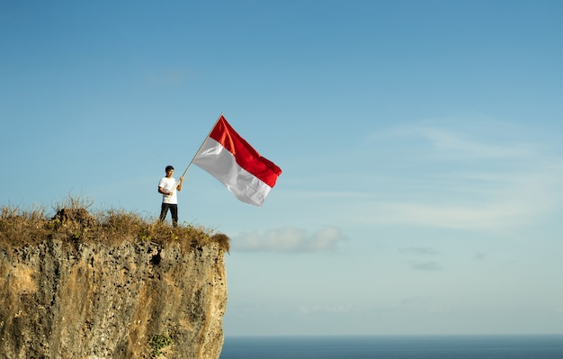 Proud indonesian man on a beach cliff raising red and white indonesia flag