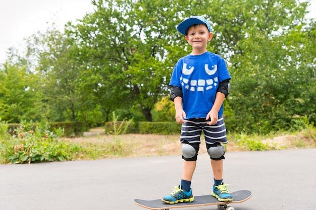 陽気な笑顔でカメラのために立ってポーズをとっている彼の新しいスケートボードを持つ誇り高き少年