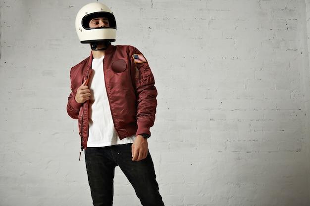 真っ白なヘルメット、ボルドーナイロンボンバージャケット、ジーンズ、白い壁の背景にtシャツを着た自慢のバイクに乗る人